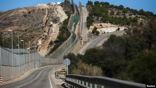 Border fence separating Morocco and Spain's north African enclave Melilla is seen along a road in the 12.5-square-kilometer territory, Dec. 4, 2013.