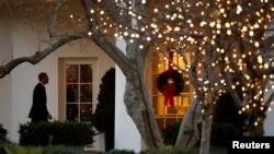កំរងផ្កាតុបតែងបុណ្យណូអែលព្យួរនៅលើទ្វារទៅកាន់ការិយាល័យប្រធានាធិបតី (Oval Office) ខណៈលោកប្រធានាធិបតីសហរដ្ឋអាមេរិក បារាក់ អូបាម៉ា ដើរត្រលប់ទៅកាន់សេតវិមាននៅក្នុងទីក្រុងវ៉ាស៊ីងតោន កាលពីថ្ងៃទី១៥ ខែធ្នូ ឆ្នាំ២០១៤។ នេះលោកប្រធានាធិបតីបារ៉ាក់អូបាម៉ាដែលជាត្រឡប់ទៅកាន់សេតវិមានក្នុងទីក្រុងវ៉ាស៊ីនតោនថ្ងៃទី 15 ធ្នូឆ្នាំ 2014 ។