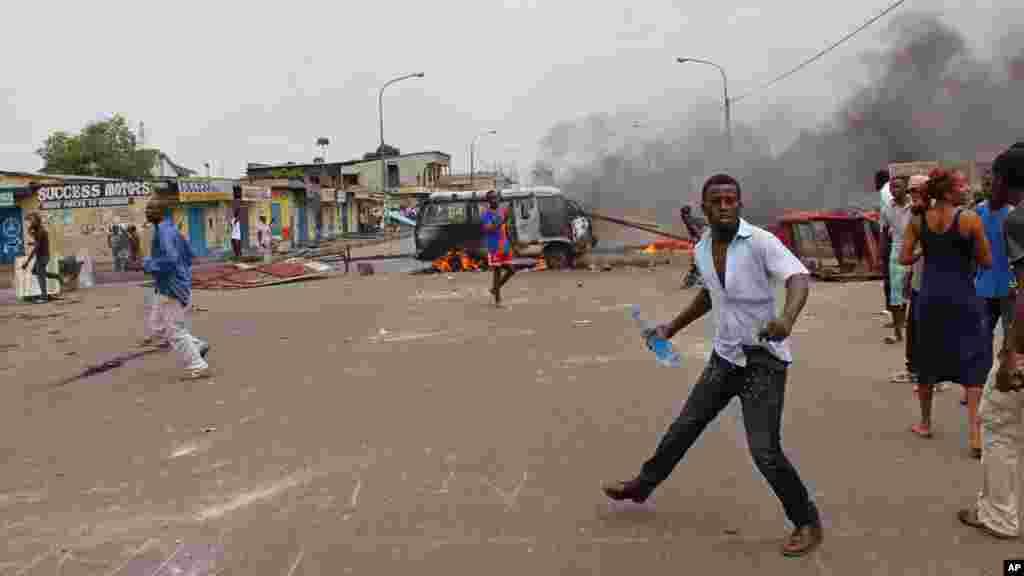 Des manifestants antigouvernementaux brûlent des pneus et un véhicule lors d'une manifestation contre la modification de la loi électorale qui pourrait retarder l'élection prévue en 2016, dans la ville de Kinshasa, République démocratique du Congo, le 19 janvier 2015.