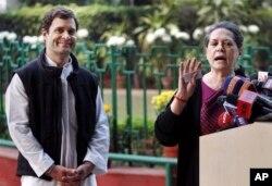 India's ruling Congress party president Sonia Gandhi, right addresses the media as Vice President Rahul Gandhi smiles in New Delhi, Dec. 8, 2013.