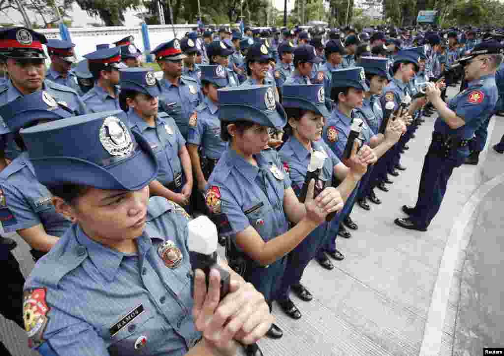 Female members of the Philippine National Police (PNP) hold service pistols covered with tape at the National Capital Region Police Office in Taguig, Metro Manila. A police officer said all policemen in the country are ordered to seal their firearms muzzles to prevent the firing of their weapons during Christmas and New Year holidays celebrations.