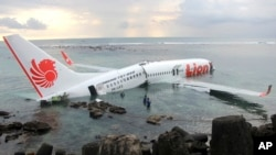 Cảnh cảnh sát và nhân viên cứu hộ dùng xuồng cứu sinh sơ tán hành khách trên chiếc máy bay Boeing 737 của hãng hàng không giá rẻ Lion Air, ngày 13/4/2013.