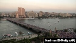 FILE - Supporters of Egypt's top military officer, Gen. Abdel-Fatah el-Sissi, march over a bridge leading to Tahrir Square in Cairo after the ouster of democratically-elected Egyptian President Mohammed Morsi, July 26, 2013.