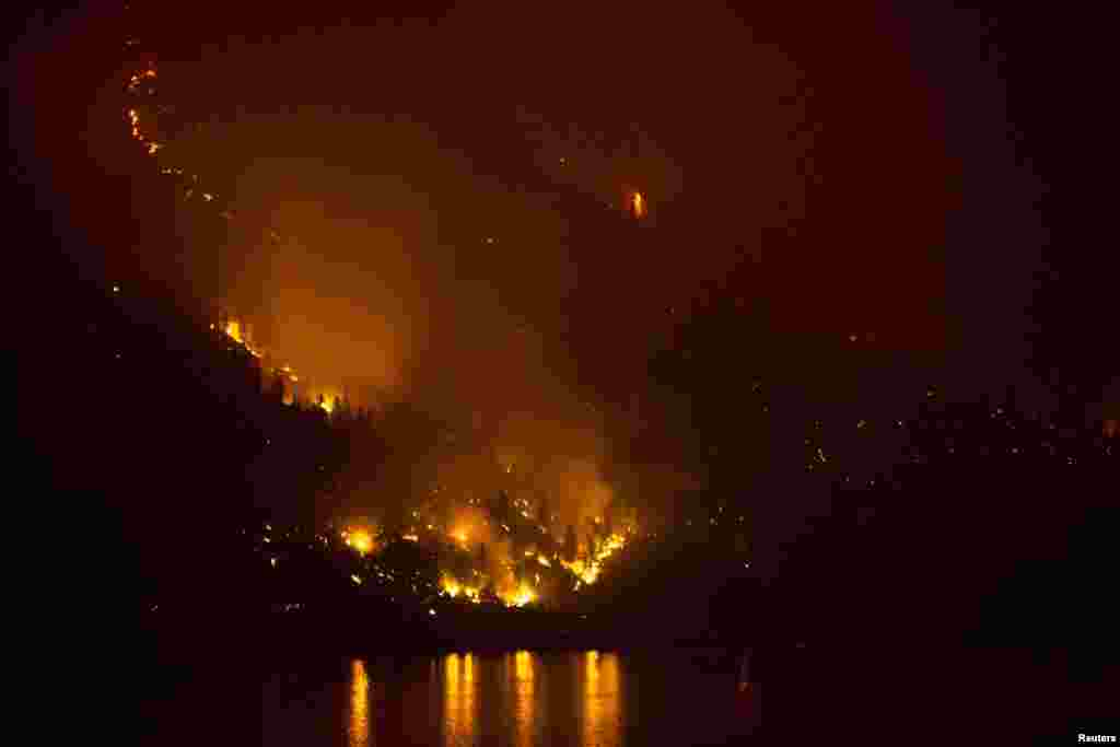 The Chelan Complex Fire in Chelan, Washington is reflected on Lake Chelan as pictured at night from Manson, Washington, Aug. 22, 2015.