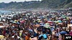 Pengunjung memadati pantai Bournemouth di Inggris selatan dan mengabaikan protokol kesehatan Covid-19, hari Kamis (25/6).