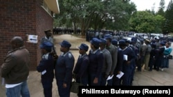 FILE: Zimbabwean police queue to vote in the capital Harare July 15, 2013. Zimbabwe's members of the uniformed forces are casting special votes in the general elections, which will take place across the country on July 31. REUTERS/Philimon Bulawayo (ZIMBABWE -