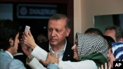 FILE - Turkish President Recep Tayyip Erdogan poses for selfie photograph with woman after voting at a polling station in Istanbul, June 7, 2015.
