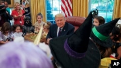 Presiden AS Donald Trump menghibur anak-anak yang mengenakan kostum Halloween di Gedung Putih, hari Jumat (27/10).
