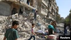 Quelques personnes ramassent leurs biens d'un site endommagé après une frappe aérienne dimanche dans le quartier d'al-Qaterji assiégé par les rebelles, à Alep, en Syrie, 17 octobre 2016 rebelle.