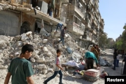 FILE - People remove belongings from a damaged site after an air strike Sunday in the rebel-held besieged al-Qaterji neighbourhood of Aleppo, Syria, Oct. 17, 2016.
