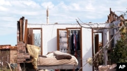 A tornado-damaged bedroom with clothes hanging in the closet is pictured in Oklahoma City, Oklahoma May 22, 2013.