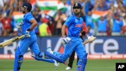 India's Virat Kohli, right, runs to complete his hundred runs during the World Cup Pool B match against Pakistan in Adelaide, Australia, Feb. 15, 2015.