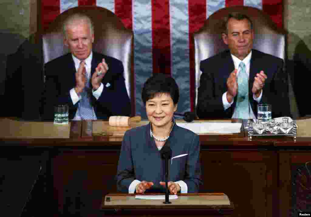 US Vice President Joe Biden and Speaker of the House John Boehner applaud South Korea President Park Geun-hye after she addressed a joint meeting of Congress in Washington, May 8, 2013.