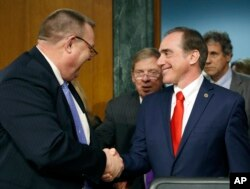FILE - The Senate Veterans' Affairs Committee Ranking member Jon Tester, D-Mont., left, with committee chairman Sen. Johnny Isakson, R-Ga., center, shakes hands with Veterans Affairs Secretary-designate Dr. David Shulkin on Capitol Hill.