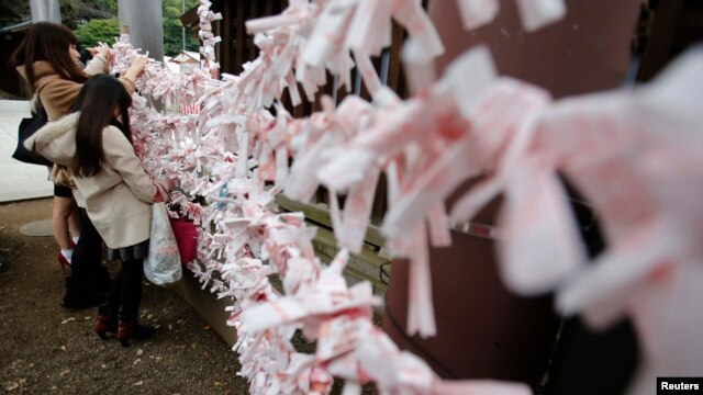 FILE - Visitors hang fortune blessing papers at Yasukuni Shrine in Tokyo.