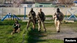 Naoružane osobe, za koje se veruje da su u službi Rusije, čuvaju stražu u vazduhoplovnoj bazi Belbek, na Krimskom poluostrvu