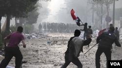 Para demonstran melempari polisi Mesir dengan batu, dalam bentrokan di dekat Lapangan Tahrir, Kairo (16/12).