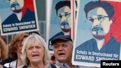 """Para demonstran memegang poster-poster dalam unjuk rasa mendukung mantan kontraktor intelijen AS Edward Snowden di Berlin (4/7). Tulisan di poster bertuliskan """"Tempat penampungan di Jerman untuk Edward Snowden"""". (Reuters/Tobias Schwarz)"""
