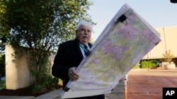 FILE - Russ Tidwell, a former lobbyist who is helping minority rights groups sue Texas over Republican-drawn voting maps, holds a set of maps as he makes his way to the federal court house, July 10, 2017.
