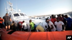 Migrants prepare to disembark in the island of Lampedusa, Italy, Aug. 7, 2013, after being rescued at sea by the Italian Coast Guard.
