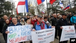 Pro-Russia demonstrators hold Russian and Crimean flags and posters as they rally in front of the local parliament building in Crimea's capital Simferopol, Ukraine, March 6, 2014.