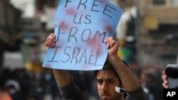 """Seorang warga Palestin mengangkat spanduk bertuliskan """"Bebaskan Kami dari Israel"""" di Hebron, wilayah Tepi Barat, Jumat, 22 Februari 2013. Warga Palestina menggelar aksi solidaritas untuk para napi Palestina yang sedang melakukan aksi mogok makan dalam penjara Israel. (AP Photo/Nasser Shiyoukhi)"""