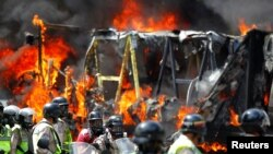 Riot security forces congregate next to a government truck that was set on fire during a rally against Venezuelan President Nicolas Maduro's government in Caracas, Venezuela, June 22, 2017.