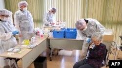 ٹوکیو میں ایک خاتون کو کرونا سے بچاؤ کی ویکیسن لگائی جا رہی ہے۔ 12 اپریل 2021
