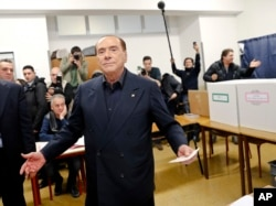 Italian former premier and leader of Forza Italia (Let's Go Italy) party Silvio Berlusconi listens to reporters at a polling station in Milan, March 4, 2018.