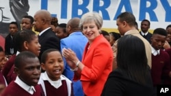 La première ministre britannique Theresa May rencontre des élèves lors d'une visite au lycée ID Mkhize à Gugulethu, au Cap, en Afrique du Sud, le 28 août 2018.