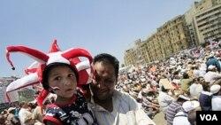 Seorang warga Mesir membawa anaknya mengikuti aksi protes di Lapangan Tahrir, di ibukota Kairo (22/7).