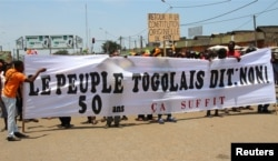 "Opposition supporters take part during a protest calling for the immediate resignation of President Faure Gnassingbe in Lome, Togo, Sept. 20, 2017. The banner reads: ""Togolese people say: No. 50 years, enough."""