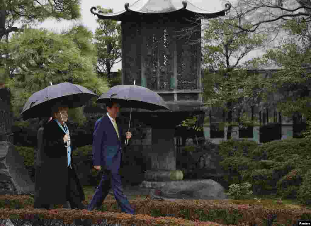 Germany's Chancellor Angela Merkel and Japan's Prime Minister Shinzo Abe walk in the gardens of the Nezu Museum in Tokyo, March 9, 2015.
