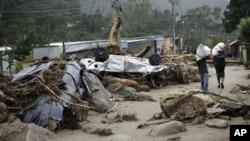 灾民走过被冲翻的汽车,逃离家园