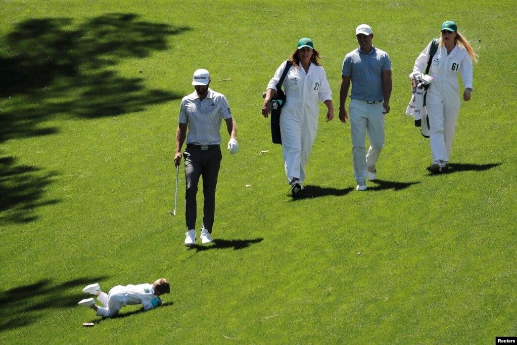 """Сын Дастина Джонсона Татум скатывается с холма, когда он присоединяется к своему отцу во время турнира 2019 Masters golf Tournament """" par 3 contest at the Augusta National Golf Club в Огасте, штат Джорджия, 10 апреля 2019 года."""
