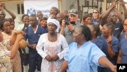 """Adama Sankoh (tengah, 40 tahun), meninggalkan pusat perawatan ebola """"Mateneh"""" di pinggiran Freetown, Sierra Leone, Senin (24/8)."""