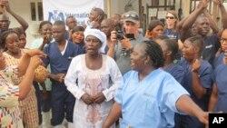 Bà Adama Sankoh (giữa), 40 tuổi, bị nhiễm Ebola sau khi con trai của bà chết vì căn bệnh này vào cuối tháng trước, đứng cùng với các quan chức y tế sau khi nhận được kết quả xét nghiệm âm tính thứ hai đối với virus này tại một trung tâm điều trị ngoại thành Freetown, Sierra Leone, hôm thứ Hai 24/8/2015.
