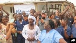 感染了埃博拉病毒的雅丹玛·桑科(中)获得治愈后在离开塞拉利昂一个埃博拉治疗中心时与医疗人员在一起。 (2015年8月24日)