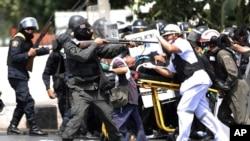 Cảnh sát dùng hơi cay, đạn cao su và đạn thật để giải tán người biểu tình gần các văn phòng của Thủ tướng Yingluck Shinawatra ở thủ đô Bangkok, ngày 18/2/2014.