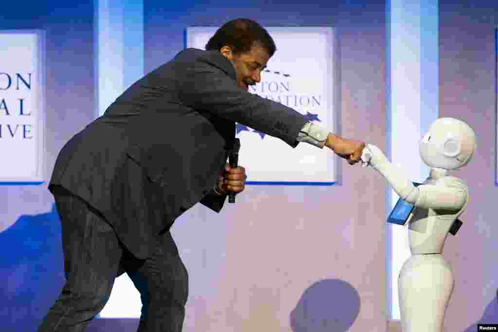 Astrophysicist Neil deGrasse Tyson interacts with Pepper, a social humanoid robot developed by Aldebaran for SoftBank, during the Clinton Global Initiative's annual meeting in New York.