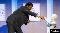 Astrophysicist Neil deGrasse Tyson interacts with Pepper, a social humanoid robot, during the Clinton Global Initiative's annual meeting in New York, Sept. 28, 2015.