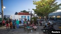 Wagonjwa na ndugu zao nje ya hospitali iliyoharibiwa na tetemeko la ardhi mjini Les Cayes, Haiti Agosti 14, 2021. REUTERS/Ralph