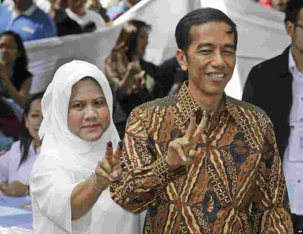 "Indonesian presidential candidate Joko Widodo, popularly known as ""Jokowi,"" and his wife Iriana, show their inked fingers after casting their ballots during the presidential election in Jakarta, July 9, 2014."