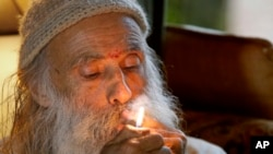 "FILE - In this Thursday, Oct. 13, 2016 photo, Swami Chaitanya lights a ""grower's joint"" marijuana cigarette at his home near Laytonville, California."
