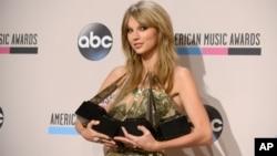 Taylor Swift posa con sus cuatro premios: album favorito (Red), artista femenina pop-rock,artista favorita, y Artista del Año.