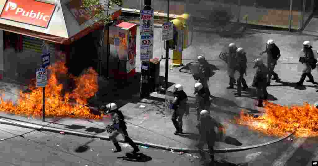 A fire bomb explodes among riot police during clashes in Athens, Sept. 26, 2012.