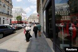 FILE - A woman wearing a headscarf walks down a street in Paris, France, July 22, 2013.