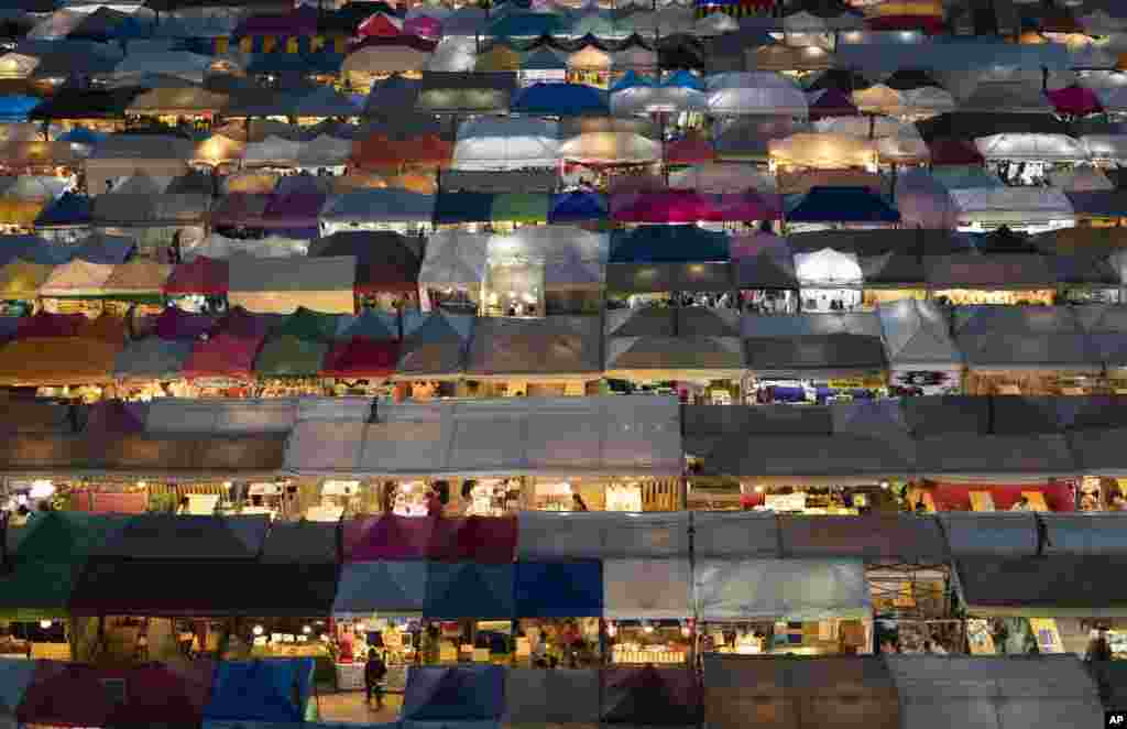 Tents of food stalls and other vendors are illuminated at Rot Fai Market in Bangkok, Thailand.