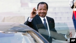 FILE - Cameroon President Paul Biya waves to reporters as he gets into his car after a meeting at the Elysee Palace, in Paris, May 17, 2014.
