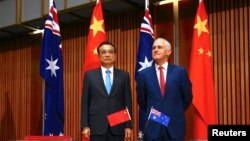 FILE - Australia's Prime Minister Malcolm Turnbull stands with Chinese Premier Li Keqiang before the start of an official signing ceremony at Parliament House in Canberra, Australia, March 24, 2017.